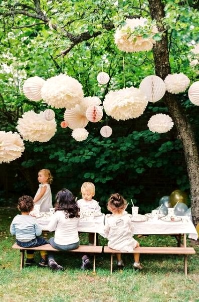 Young children sitting at a table in a garden under a tree, the tree is decororated and the table is made up for a celebration.