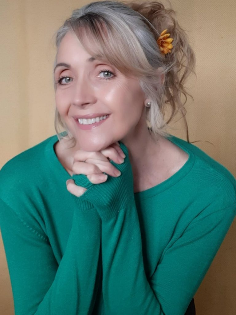 Head and shoulders portrait of Sylvia smiling. She has a flower in her hair and is wearing a green jumper.