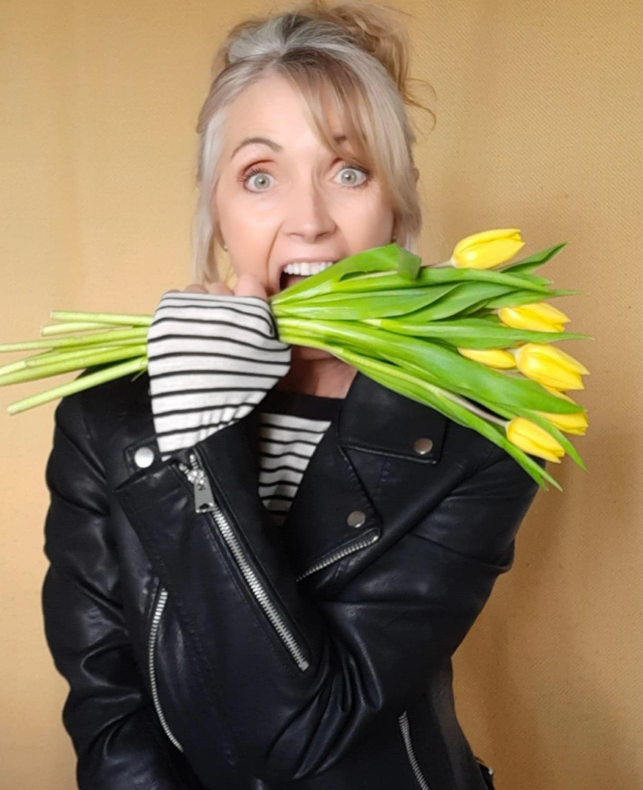 A portrait photo of Sylvia holding a bunch of daffodils.