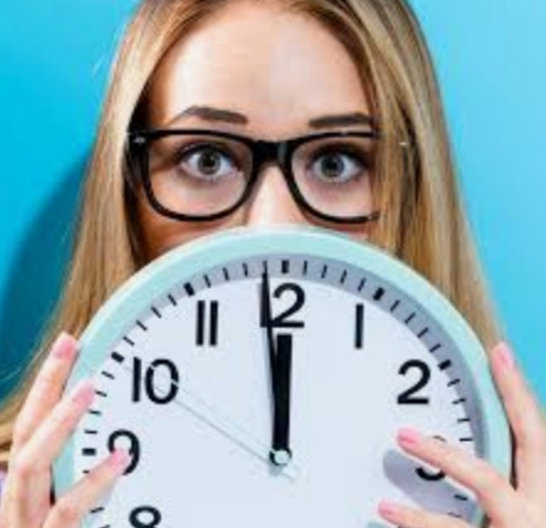 A womans face appearing over a clock