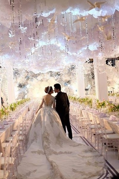 Photo taken from behind of a Bride and Groom walking through an aisle of reception tables. The bride's dress is white with an very long train.