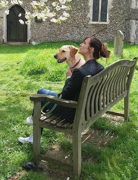 Sylvia sitting on a park bench with a Golden Labrador called Luna